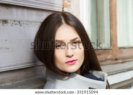 Young girl on a background of an old wooden house