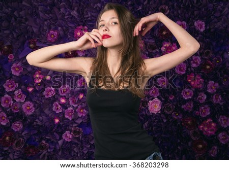 Young girl on a background of purple flowers. Emotional portrait of a woman. Cheerful and happy teenager girl with long hair. - stock photo
