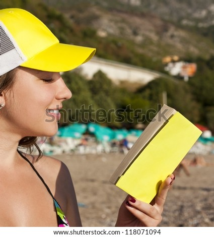 Young girl on a beach reads a book - stock photo