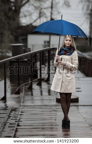 Young girl on a bridge on a cloudy rainy day - stock photo