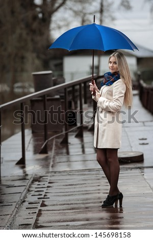 Young girl on a bridge on a cloudy rainy day