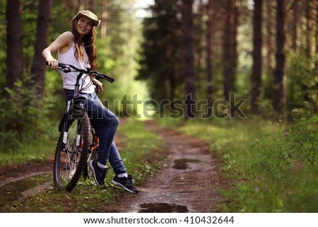 young girl on a sports bike in a summer forest - stock photo