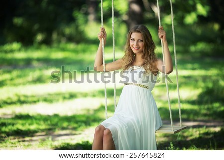 Young girl on a swing - stock photo