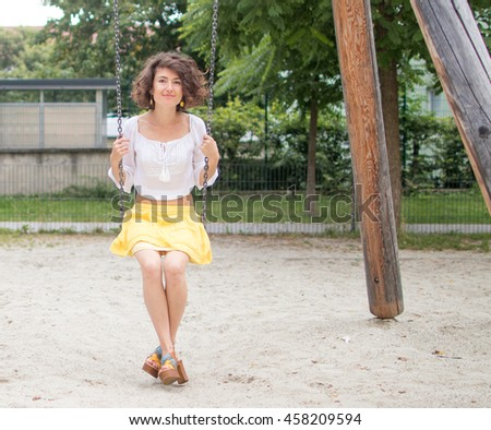 Young Girl on a Swing in a Public Park