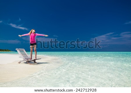Young girl on a tropical beach with outstretched arms standing on chair - stock photo