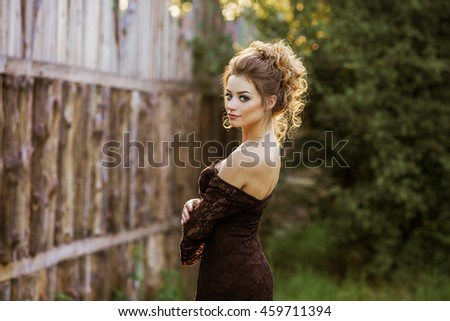 Young girl on background of the old wooden fence. Vintage