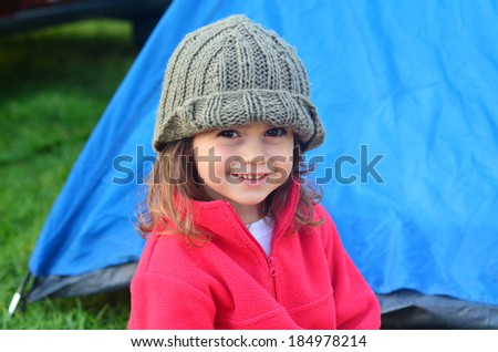 Young girl on camping holiday smiling while looking at the camera, relaxing outside a tent outdoor. Concept photo of child , children, camping, outdoor, nature, adventure, holiday. - stock photo