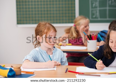 Young girl on class looking at a classmates work as they sit side by side at a desk with a serious expression of concentration - stock photo