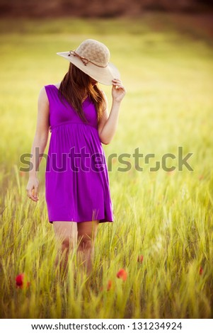 Young girl on field hiding behind her hat.