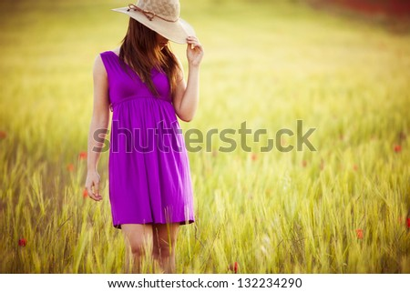 Young girl on field hiding behind her hat. - stock photo