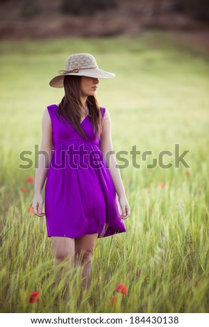 Young girl on field hiding her eyes below her hat. - stock photo