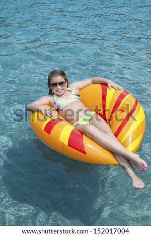 Young girl on float in pool  - stock photo