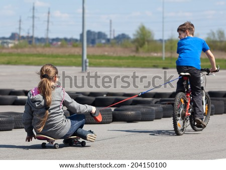 Young girl on skateboard following little boy on bicycle in a sports track - stock photo
