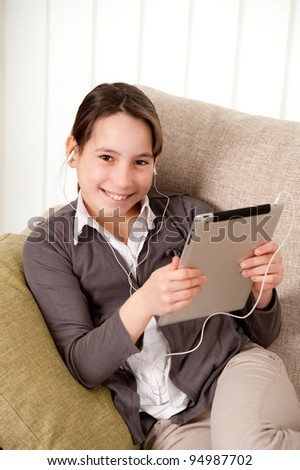 young girl on sofa  with touch tablet computer - stock photo