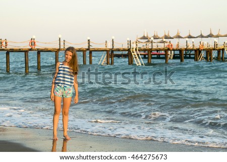 young girl on the beach near the wooden pier