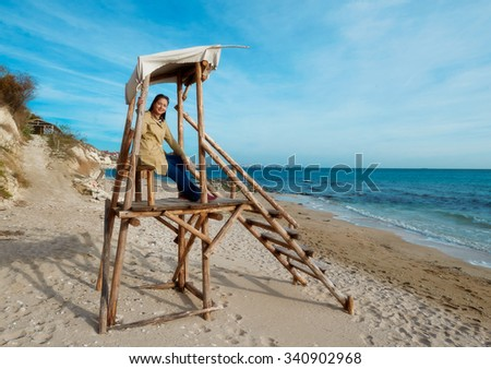 Young girl on the beach sitting on a wooden structure for rescuers - stock photo
