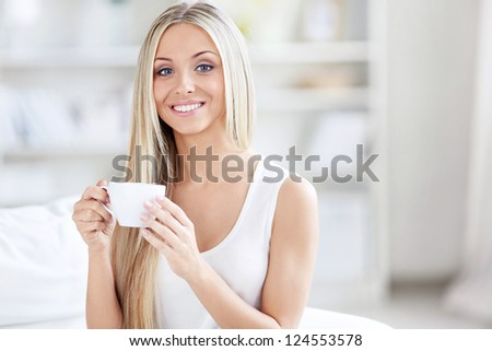 Young girl on the couch with a cup