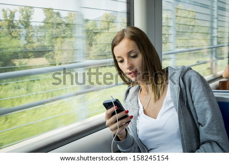 young girl on the public transportholding mobile cell - stock photo