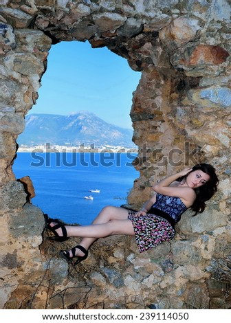 Young girl on the ramparts near the sea - stock photo
