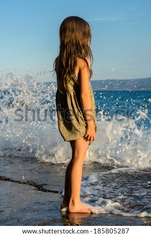 Young girl on the sea coast  at sunset time