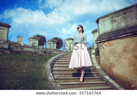 Young girl on the stairs. Fashion style portrait of a beautiful lady - stock photo