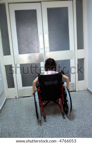 Young girl on wheelchair in front of closed doors
