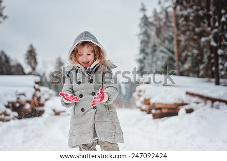 Young girl on winter walk having fun and looking at her gloves with tree felling on background - stock photo