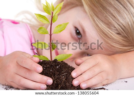 Young girl or child with a  plant while smiling, isolated on white. - stock photo