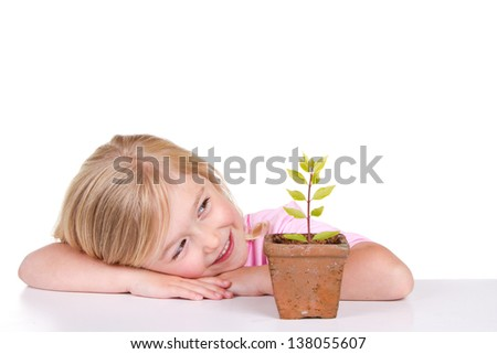 Young girl or child with a potted plant while smiling, isolated on white.