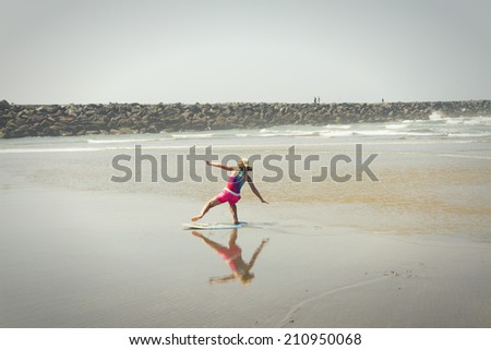 Young girl or teen learning to ride a skimboard on the Oregon coast.