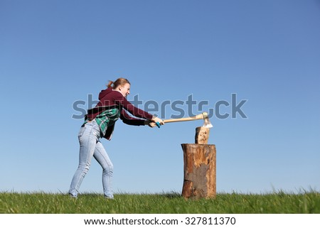 Young girl outdoors chopping wood with blue sky