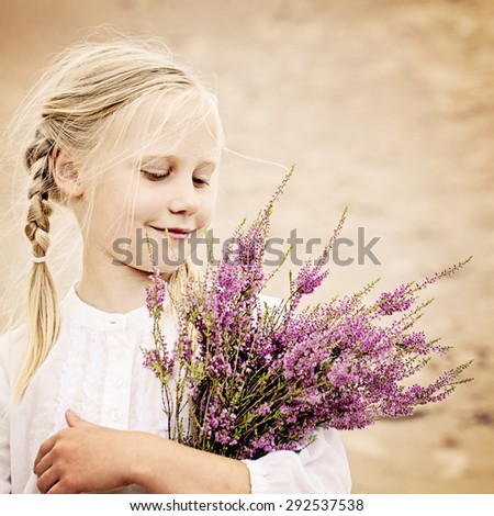 Young Girl Outdoors. Happy Girl with Heather Flowers in Great Britain Heath - stock photo