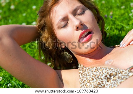 Young girl outdoors holding an ice cube in her mouth. Cold drops fall on her body. Heat concept. - stock photo