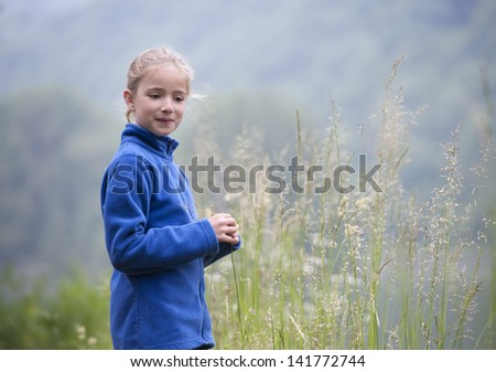 young girl outdoors playing with grass sprites