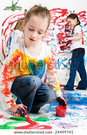 Young girl painting the floor with two children in the background - stock photo