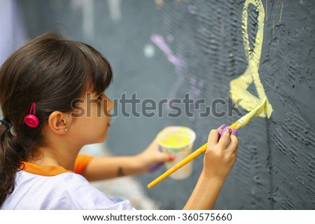 Young girl paints the  wall, outside - stock photo