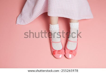 Young girl pastel pink outfit from above. Skirt and legs in white socks and flats shoes. Background layout with free text space. - stock photo