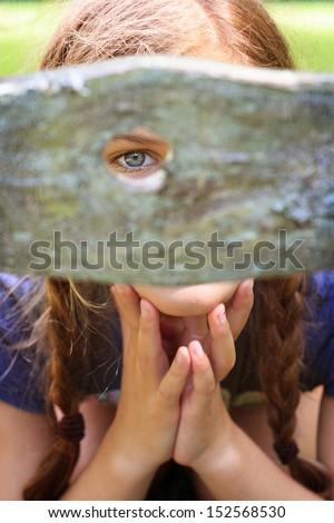 Young girl peeking through hole in fence - stock photo