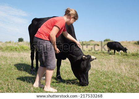 Young girl petting a friendly cow outdoors - stock photo