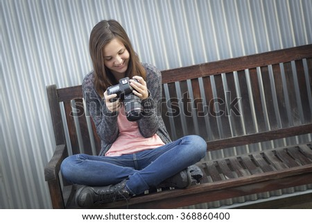 Young Girl Photographer Sitting on Bench Looking at Back of Camera. - stock photo