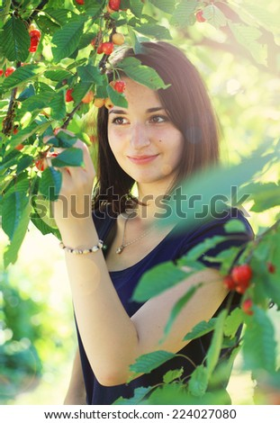 Young girl picking cherry outdoor from cherry tree - stock photo