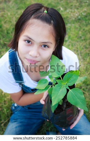 young girl planting tree in garden - stock photo