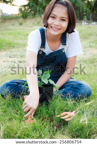 young girl planting tree in garden