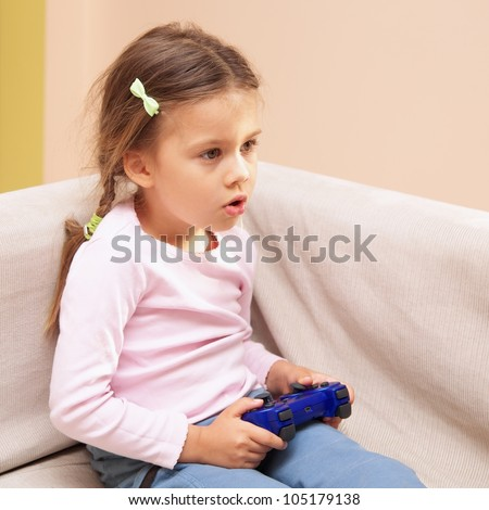 Young girl playing a video game with a blue controller - stock photo