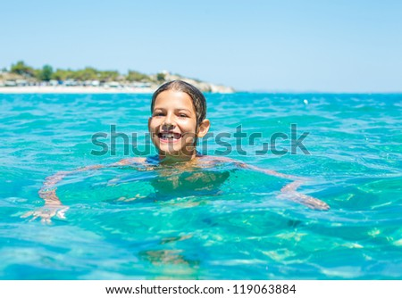 Young girl playing and swimming in the transparent sea - stock photo