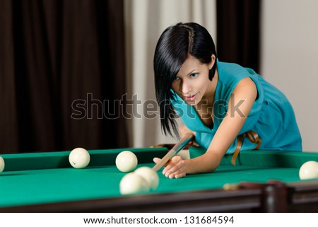 Young girl playing billiard. Spending free time on gambling - stock photo