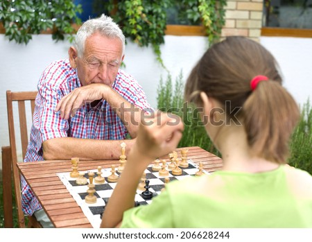 Young girl playing chess with her grandfather in garden - stock photo