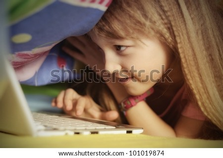 Young girl playing computer game secretly - stock photo