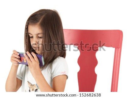 Young girl playing game on phone sitting - stock photo