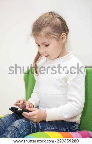 Young girl playing game on the cellphone, sitting indoor - stock photo